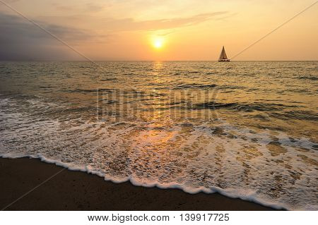 Sailboat sunset is a silhoueette of a boat sailing with a colorful sunset sky and the ocean waves breaking on the sea shore.