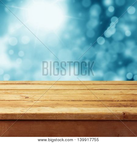 Empty wooden deck table with winter bokeh background. Ready for product display montage. Christmas background