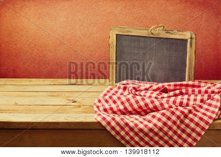 Empty wooden table with chalkboard and tablecloth over grunge red wall