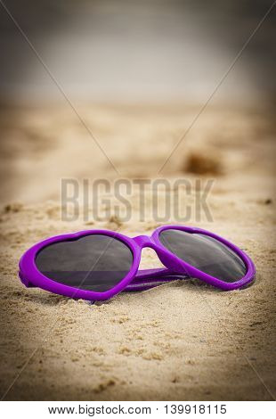 Purple funny sunglasses in shape of heart lying on sand at the beach vacation and summer time eye protection