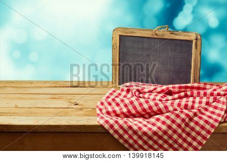 Empty wooden table with chalkboard and tablecloth over winter bokeh