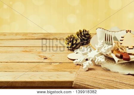 Christmas table setting with plate fork and knife ornaments on wooden table