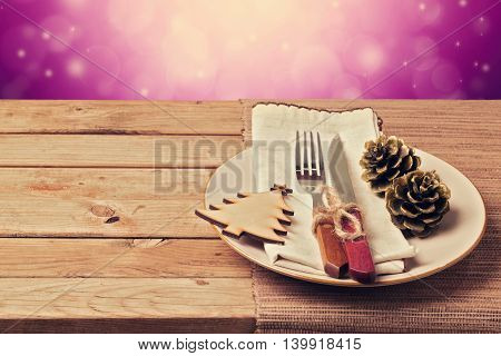 Christmas retro table setting with wooden ornaments plate fork and knife over purple bokeh background