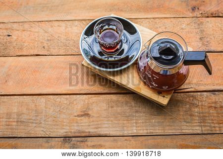 hot coffee cup and pot on wood table in coffee shop.