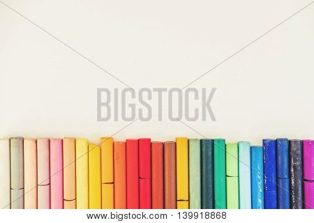 Colorful pastel oil crayon lines up, on white background with copy space
