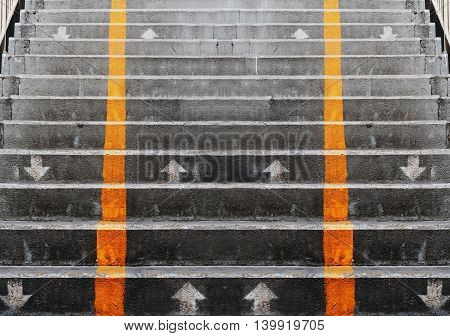 Abstract concrete stairs with yellow diving vertical lines and direction arrows
