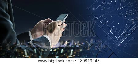 Businessman using mobile phone with city at night and blueprint architectural drawing plan