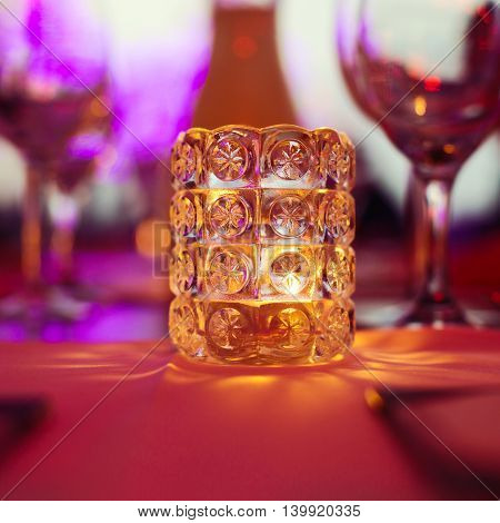 Candle on restaurant table over bokeh background