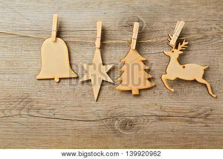 Christmas toys hanging on string over wooden background