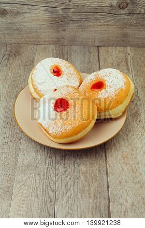Donut for jewish holiday hanukkah on plate on wooden background