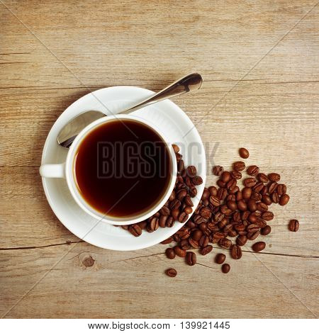 Coffee cup and coffee beans on wooden table. View from the top