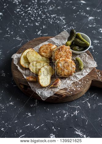 Fish balls and baked potatoes on wooden cutting board on dark background