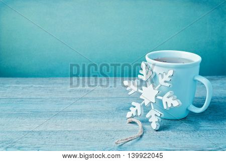 Winter drink with wooden snowflake decoration on wooden table