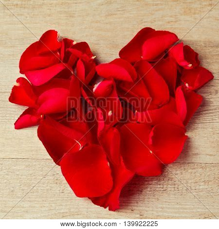 Heart shape made from rose flower petals on wooden background. Valentine's Day greeting card