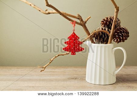 Winter branches with Christmas decoration tree in white jug