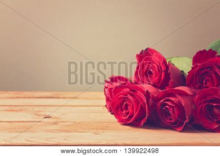 Background with red roses on wooden table