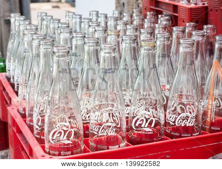 BANGKOK, THAILAND - JUNE 25: Empty recycle bottles of Coca Cola in red plastic box on June 25, 2016 in Bangkok, Thailand. Coca Cola drinks are produced and manufactured by The Coca-Cola Company