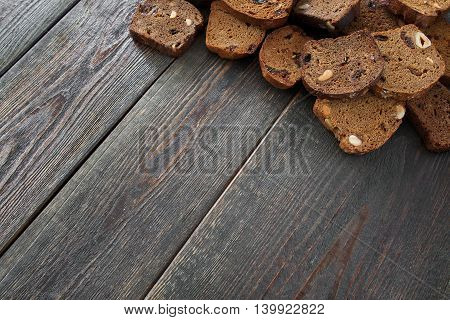 Wooden background with rye bread slices, copyspace. Rustic bakery workplace, free space for text or advertisement