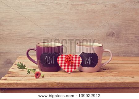 Couple of tea cups with chalkboard stickers over wooden background