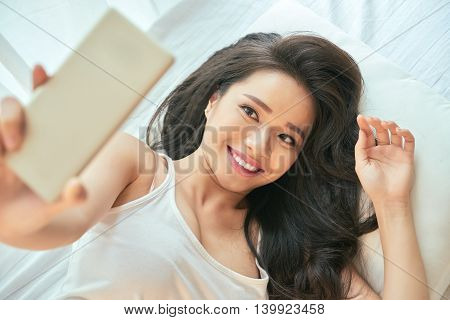 Attractive Vietnamese girl lying in bed and taking selfie