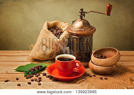 Cup of hot coffee and grinder on wooden table