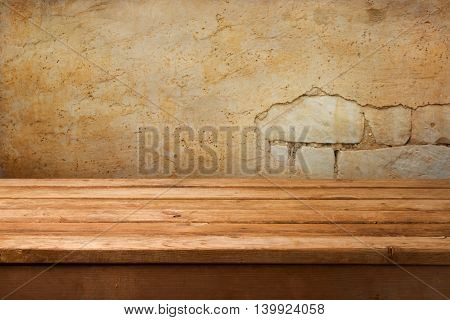 Grunge interior background with wooden table over brick wall