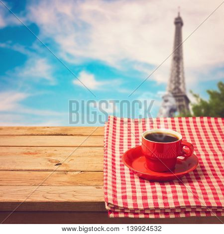 Coffee cup with checked tablecloth on wooden table over Eiffel tower in Paris France