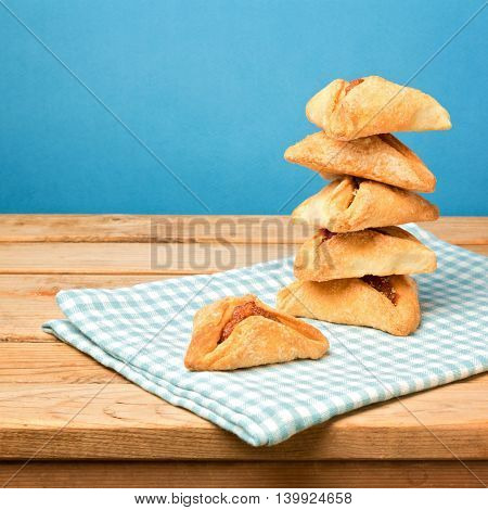 Hamantaschen cookies for Jewish festival of Purim on wooden table over blue background