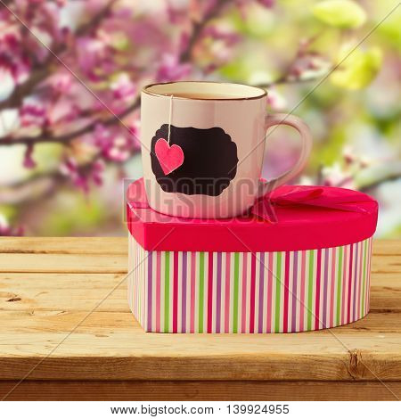 Cup of tea with heart shape and gift box over spring background. Valentine's day concept