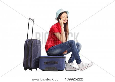Young woman sitting on her luggage and talking on cell phone isolated on white background