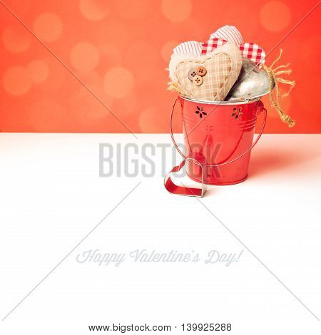 Valentine's day heart shapes in bucket on white table