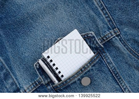 A blank notebook and pen in workmans jeans pocket. Top view