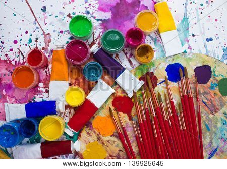 Paints, brushes and palette on watercolor painted background. The workplace of the artist. Banner for school