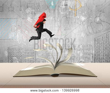 Businessman Holding Red Arrow Sign Running On Open Book