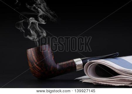 Smoking pipe on a black
