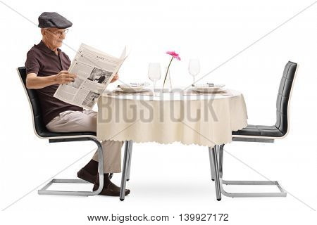 Senior man reading a newspaper seated at a restaurant table isolated on white background