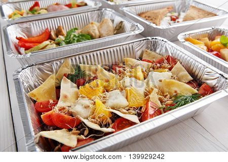 Healthy food and diet concept, restaurant dish delivery. Take away of fitness meal. Weight loss nutrition in foil boxes. Salad with cod fish, wheat sprouts and crispy tortilla pieces at white wood