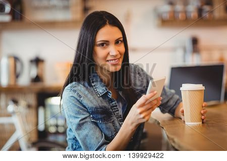 Young woman using mobile phone while having coffee at office cafeteria