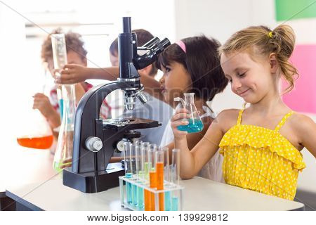 Smiling girl holding chemical in laboratory