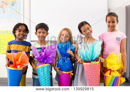 Portrait of smiling multi ethnic children holding artwork in classroom