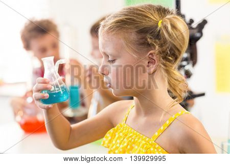 Close-up of thoughtful girl looking at chemical in laboratory