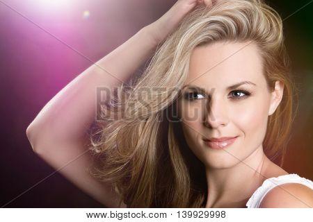Beautiful blond woman in pink spotlight