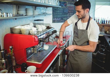 Handsome male worker using strainer while standing by espresso maker at cafe