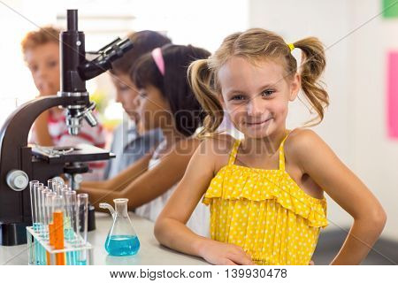 Portrait of smiling girl with classmates in laboratory
