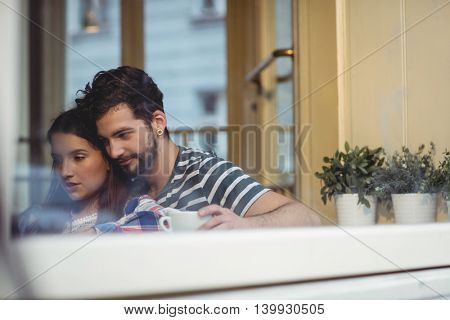 Young couple bonding over coffee at cafe