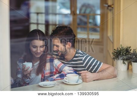 Cheerful young couple talking at coffee shop