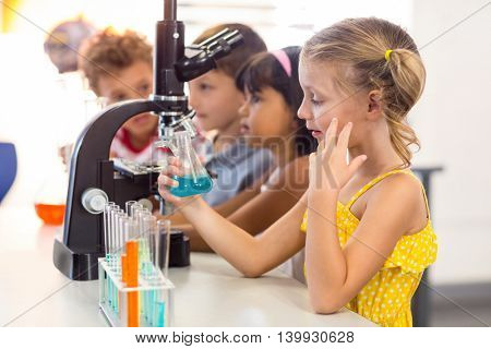Thoughtful girl looking at chemical in laboratory