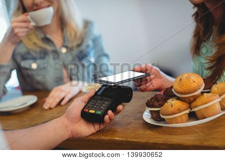 Female customer paying through technology at cafe