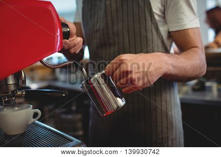 Midsection of male barista using espresso maker at coffee house