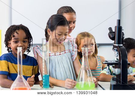 Smiling schoolchildren with scientific equipment in lab at school